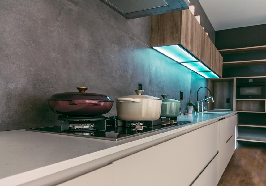 View of a modern kitchen with several pots on the stove against a grey microcement like backsplash.