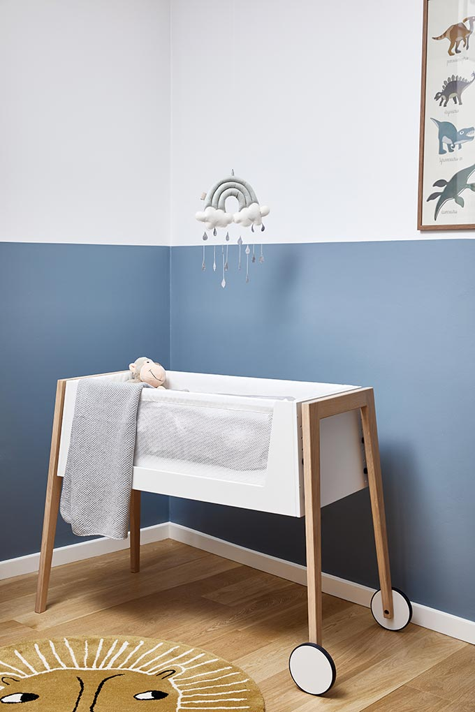 A cot bed in a baby nursery room with color blocked blue walls. Image by Cuckooland.