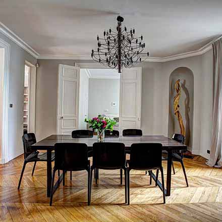 A stylish interior with a black dining table and chairs, black chandelier with a chevron pattern hardwood floor