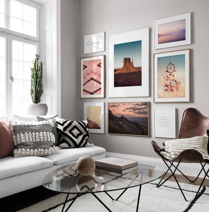 A contemporary bright living room with a white sofa and glass top round coffee table, featuring a gallery wall. Image by Desenio.