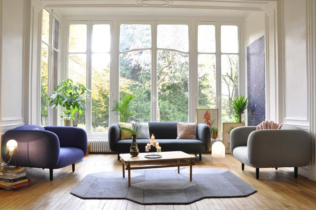 A very bright living room with a gray three seater sofa and two armchairs with a coffee table in the middle atop a irregular shaped rug. The background is a series of glass doors from floor to a very high ceiling