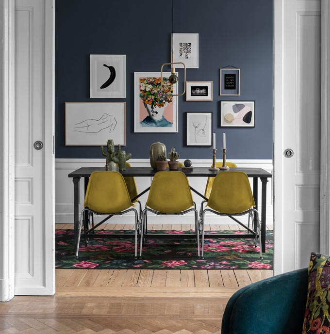 A stylish dining space featuring a blue accent wall with an art gallery. Image by Desenio.