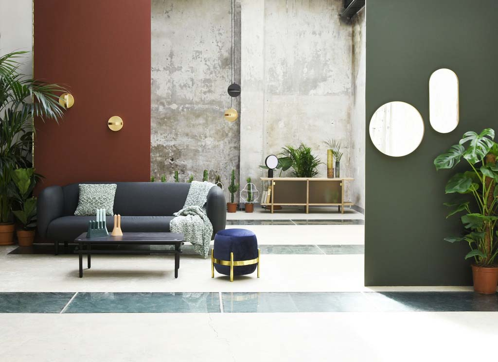 A spacious setting with a gray sofapartially against a dark burgundy wall with a black coffee table and decor on it, while there is a wooden sideboard in the background against a concrete wall. There is a white marble flooring with bands of black marble forming a pattern