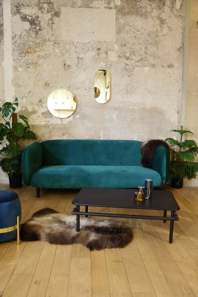 Blue teal velvet sofa against a concrete wall with planters on either side and a black coffee table. There is hardwood flooring with a fur rug on it