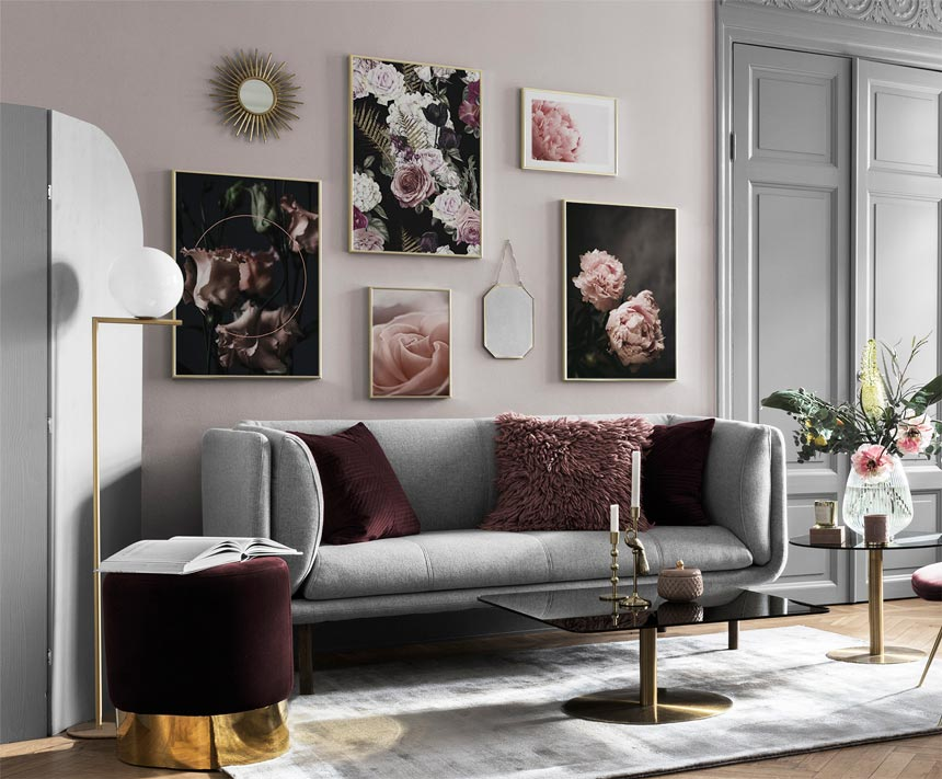 A perfect example of an art gallery wall in a stylish grey living room with burgundy accents, that sports a combination of art images hanging from a wall and mirrors. Image via Desenio.
