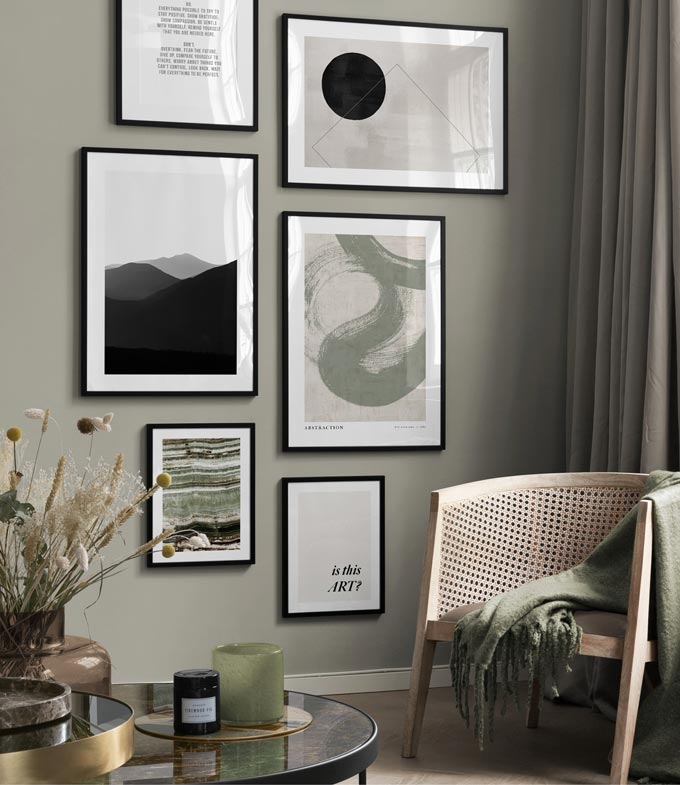 A gallery wall with art prints. A cane armchair with a muted green throw and a dark marble top round table with decor set the organic but eclectic vibe. Image via Desenio.