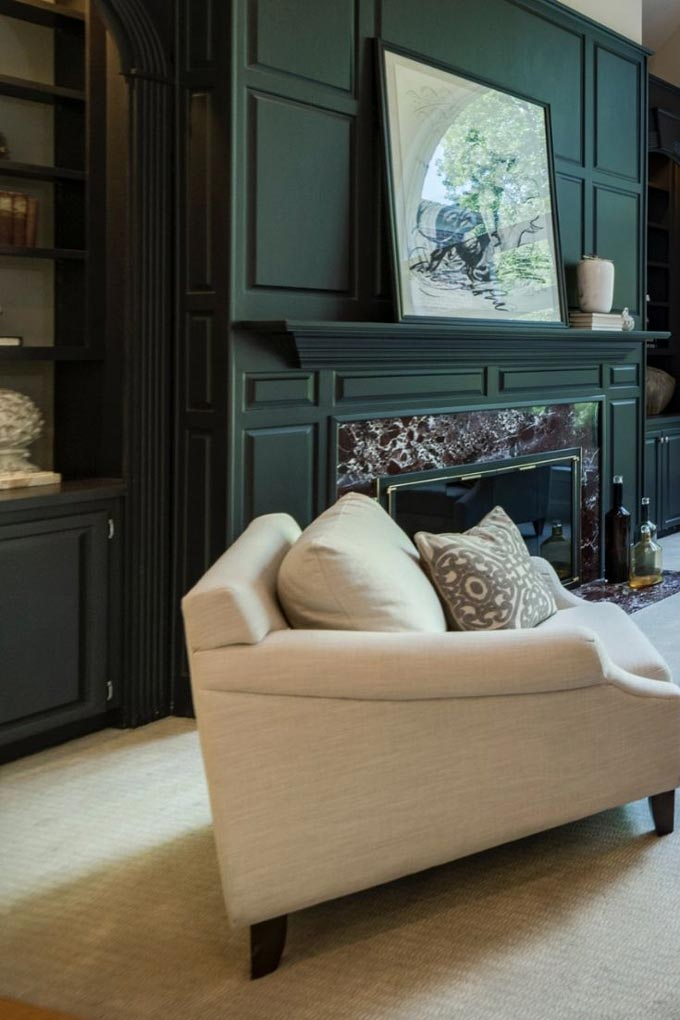 Partial view of a living room with an dark green accent wall that features a fireplace.