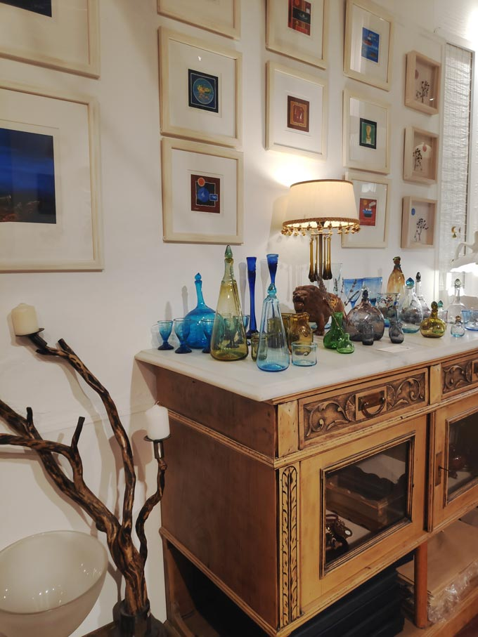 View of an orderly gallery wall with art images over a vintage upcycled credenza. Image by Velvet.