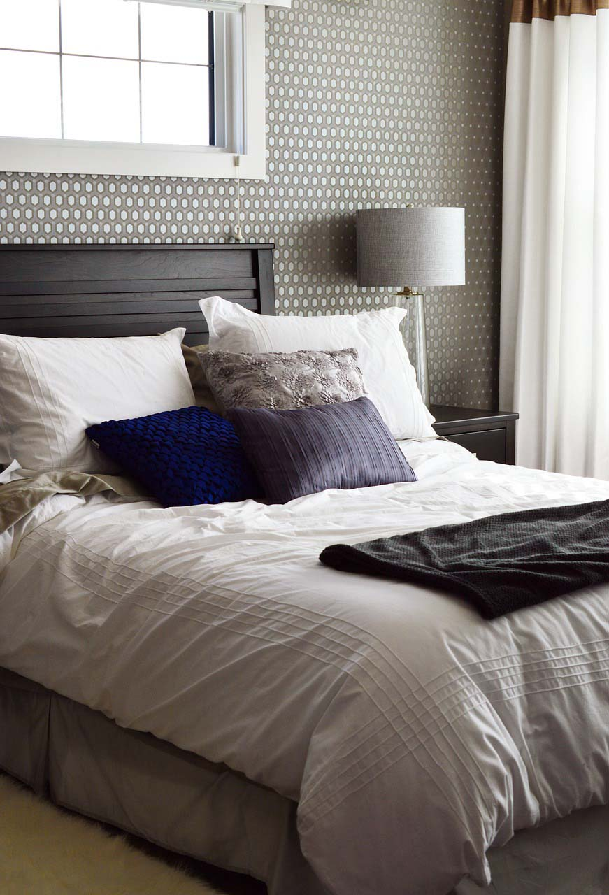 A simple but stylish bedroom with a gray pattern wallpaper as an accent