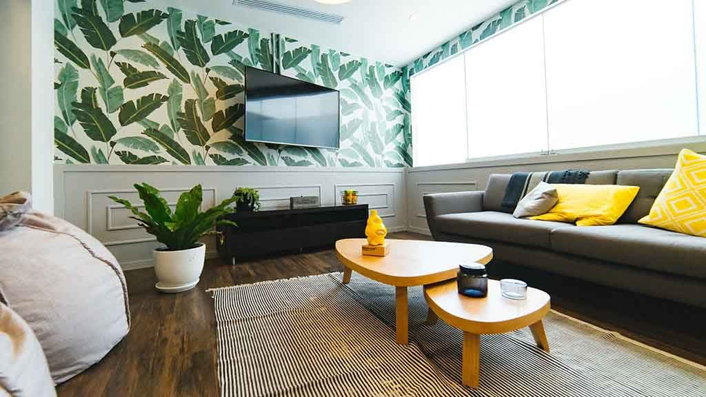 A minimal living room with a vibrant green leaf pattern wall covering as an accent
