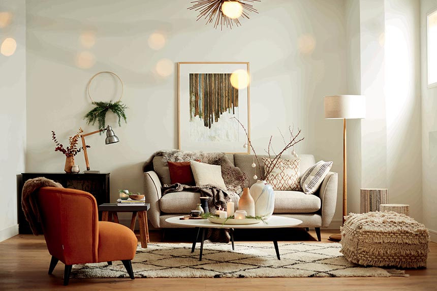 A contemporary living room with an off white sofa, paired with a rusty armchair. Image by DFS Furniture.