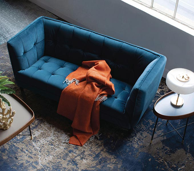 A blue velvet sofa with a side table next to it and a rusty hue throw on it. Image by Harvey Norman.