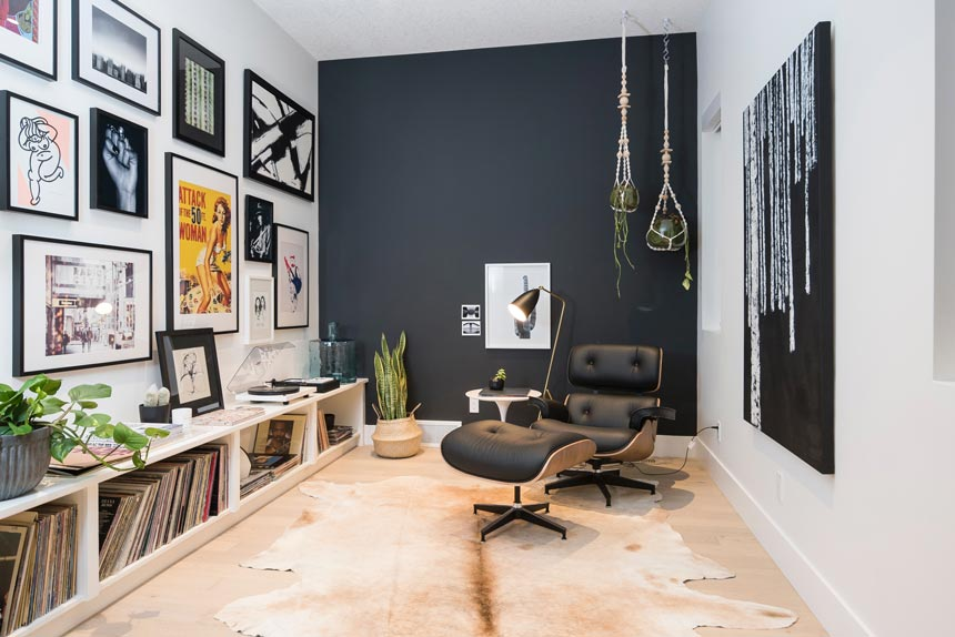 A contemporary setting with an Eames lounge chair, a dark grey accent wall in the background and a art gallery wall.