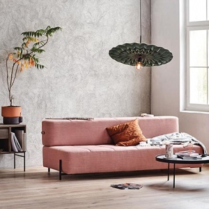 A pink modern sofa bed in a warm minimal setting. Image by Nest.