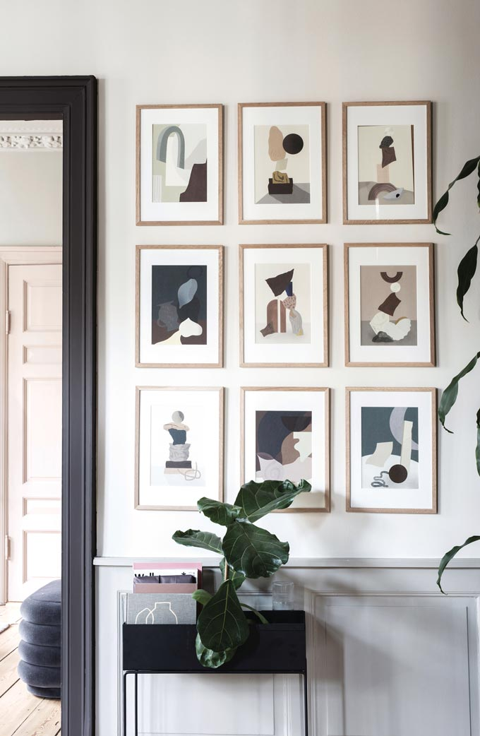 An art gallery wall above a black Ferm Living planter box. Image by Nest.