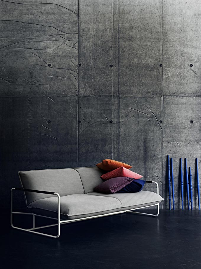 That is an jaw dropping grey sofa bed with a sleek frame to it against a concrete wall. Image by Nest.co.uk.