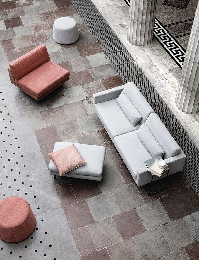 A beautiful minimal light gray sofa and pouf along with an armless chair as seen from above. Image by Nest.co.uk.