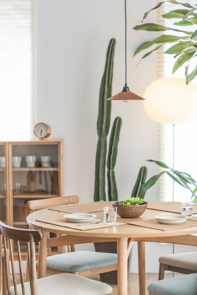 A wooden round dining table and chairs set for a meal with a very tall cactus plant in the background as decor