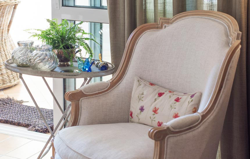 A vignette by a window door, with a vintage armchair, a side table and decor adding pops of color in this neutral palette scheme.