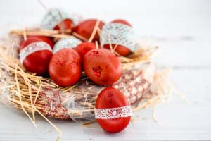 red easter eggs in a nest of hay, tied a lace ribbon, close-up , lying on a white wooden background still life