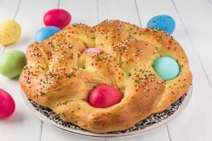close up of baked easter bread with colorful eggs on a plate.