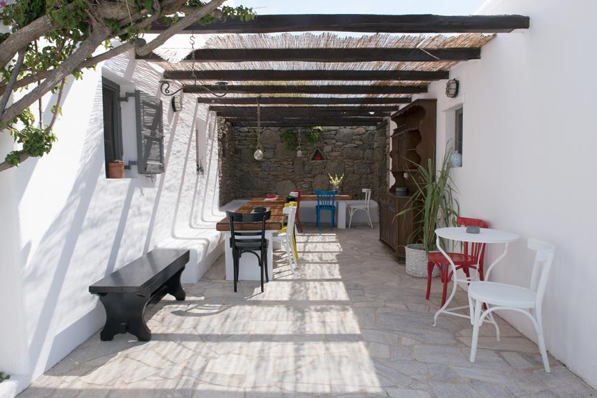 An outdoor dining setup sheltered by the sun via a pergola. In the background there is a masonry accent wall, pops of bright colors and a mix of different woods make up the rest of the decor in this Mykonian house.