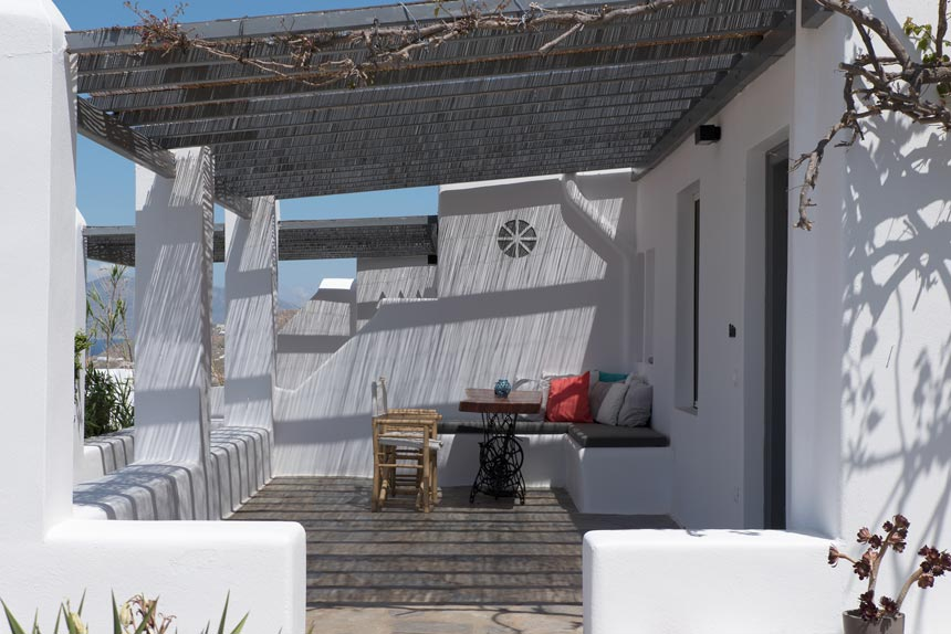 An outdoor veranda in a Cycladic dwelling with a pergola atop.
