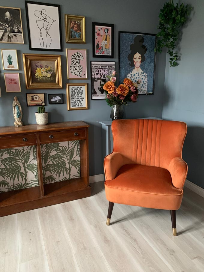 A burnt orange armchair looking great against the blue gray walls and the wooden sideboard, making a cozy vignette. Image by Cult Furniture.