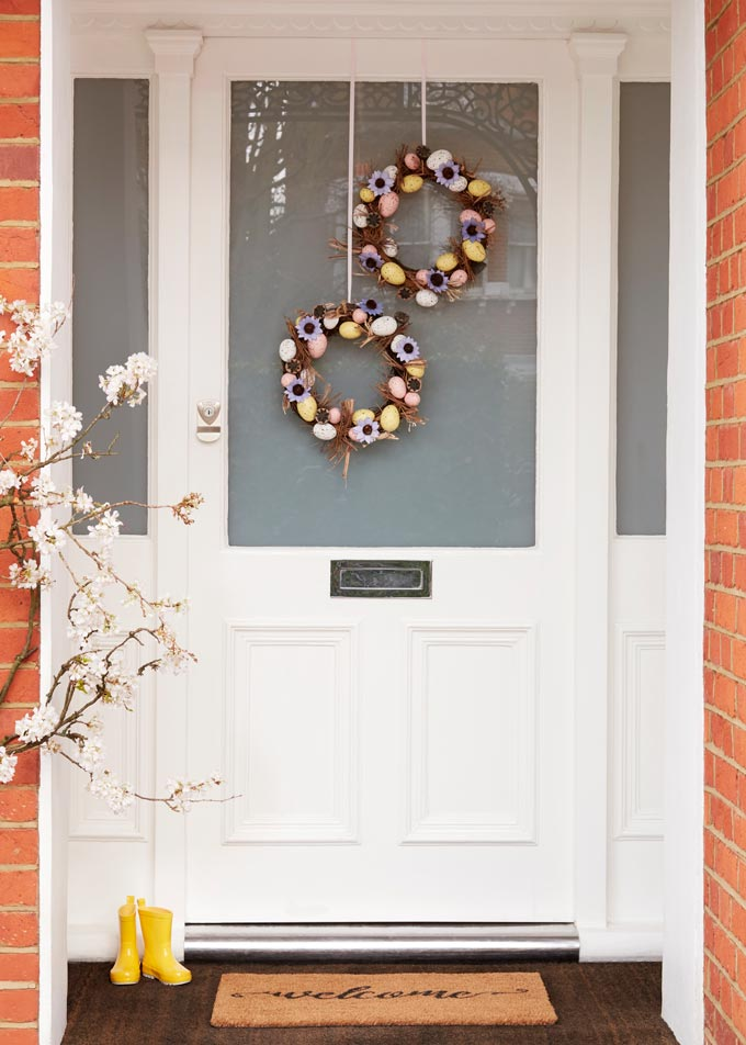 A white front door decorated with two wreaths for Easter celebrations. Image via John Lewis.