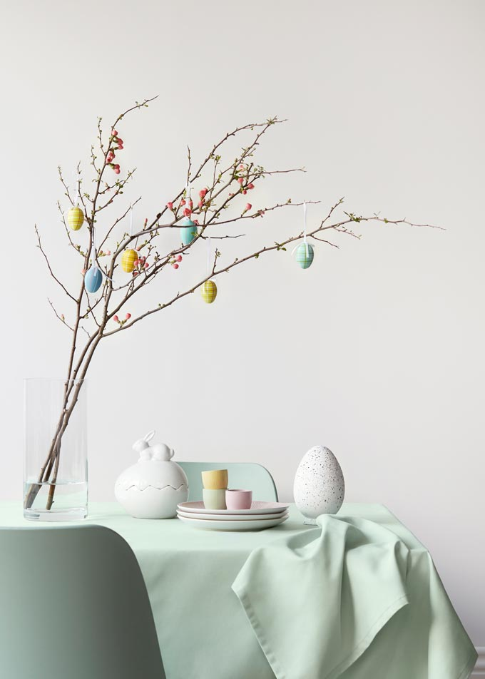 Easter decorations in pastel hues including a glass vase with a branch and eggs hanging from it. Image by John Lewis.