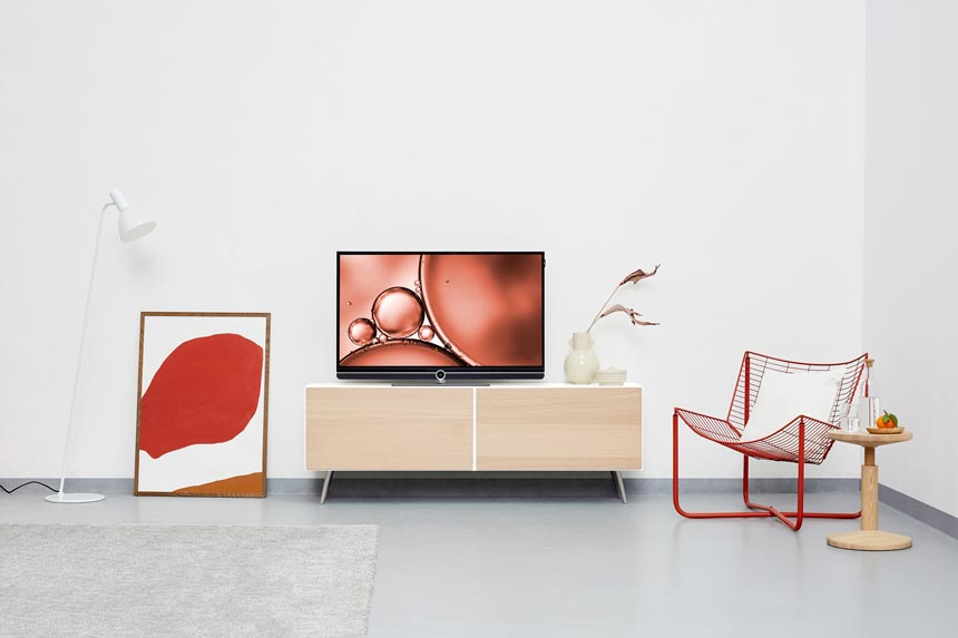 A minimal setting with an armchair, side table, sideboard with TV, a white floor lamp and an art image up against a wall.