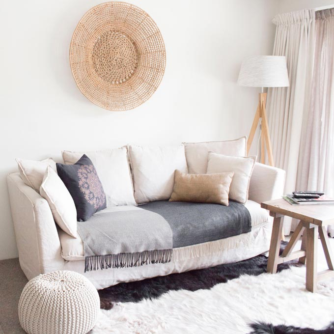 Maximalism in interior design is trending and effecting minimal interiors too. A neutral off white minimal Scandi living room with an organic vibe to it using a big straw hat as an accent over the off white sofa.