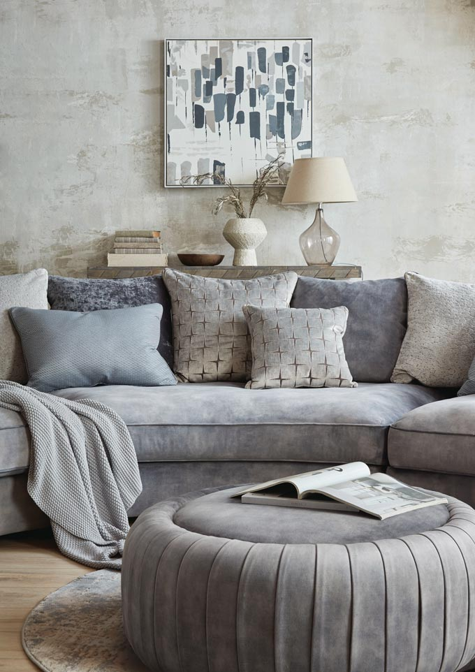 A beautiful curvy sofa, the Palm by Sofology, looking lushious with a whole lot of decorative pillows, a pouf and console table behind it. Image via Sofology.