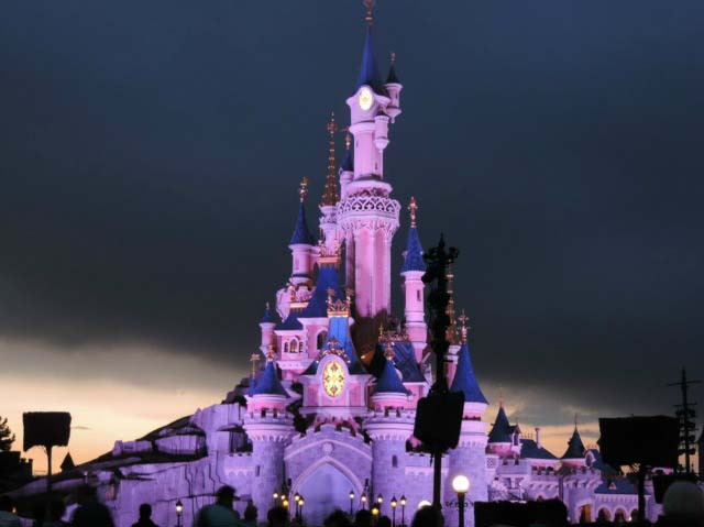 Disney's castle in Disneyland Paris after sunset hours, lit in purplish hues.