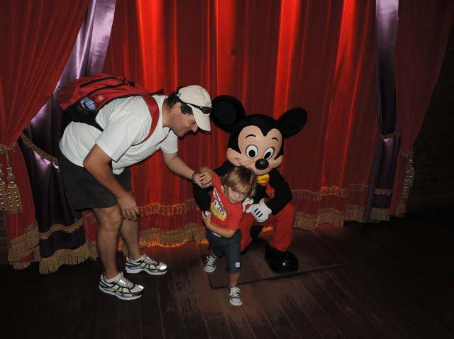 Husband and son with Mickey Mouse. Son trying to get away from Mickey