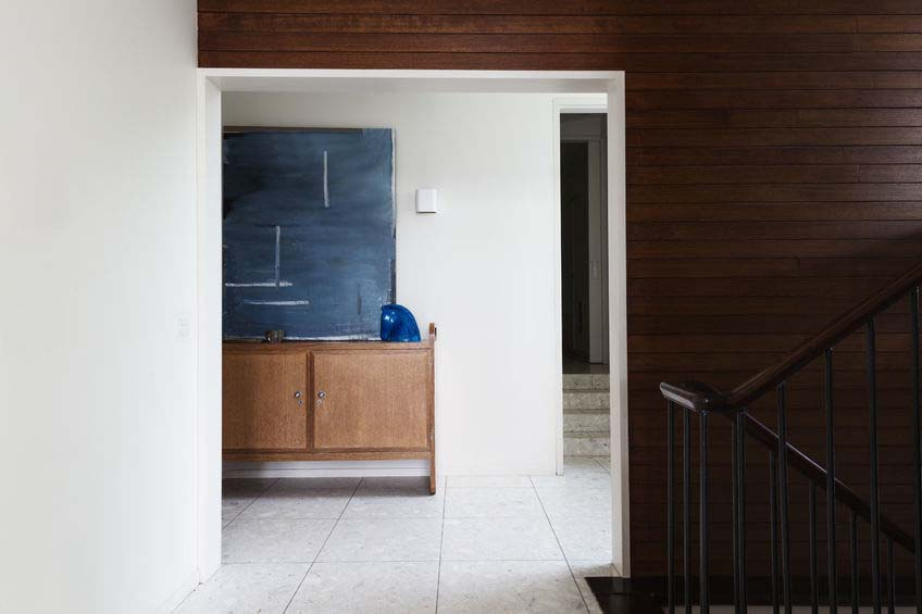 wood panel wall detail and entry foyer in mid century modern australian home with terrazzo floor tiles
