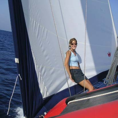 Velvet leaning against a sail while on a sailing trip