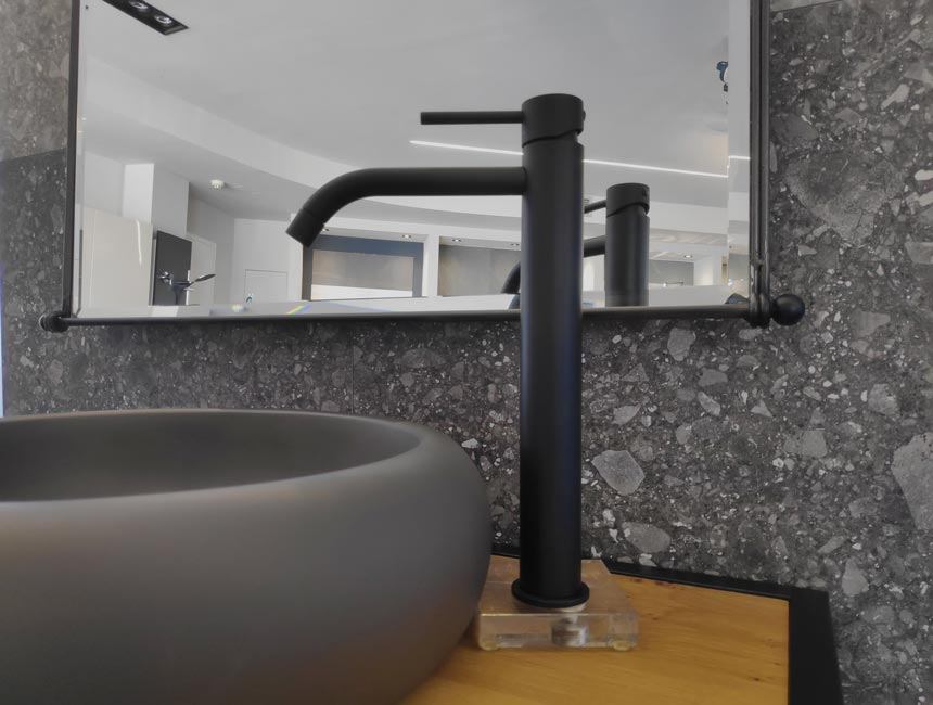 Detail of a wooden bathroom vanity with a black faucet, steel frame mirror and terrazzo backsplash.