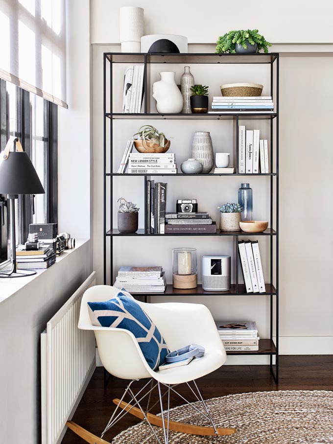 A contemporary styled vignette with a rack of bookshelves next to a window and an armchair. Image by John Lewis.