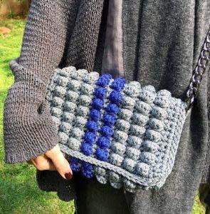 Detail view of a handmade grey crochet bag