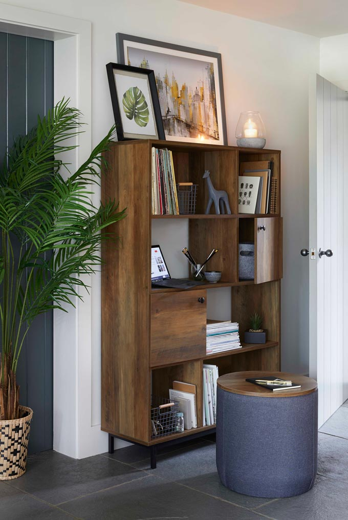 A wooden bookcase unit styled beautifully. Image by Dunelm.