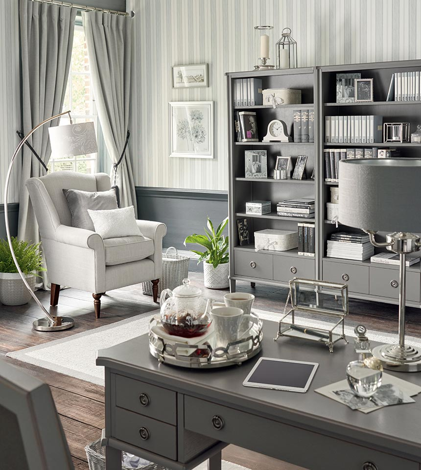 A home office with bookcase units, a white armchair, a grey French style desk and a very grey color palette governing everything. Image by Laura Ashley.