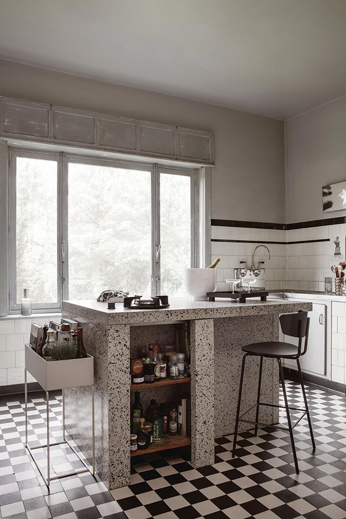 A kitchen with a tiled black and white patterned floor and a terrazzo island. Next to stands the Ferm living planter box. Image by Nest.