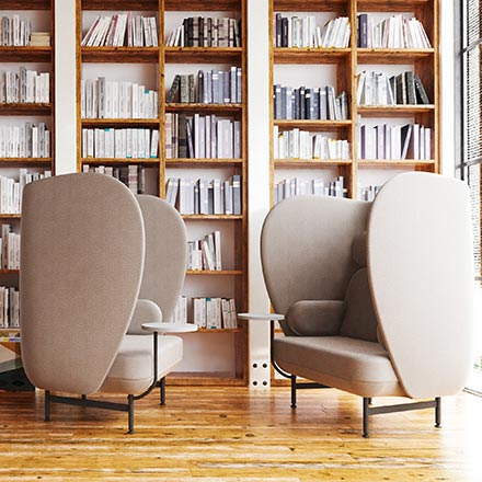 A large home library room with two Fritz Hansen Plenum armchairs that make a huge statement yet provide an incredible sense of discreteness. Image by Nest.