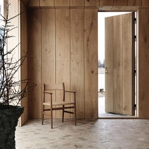 The Brdr. Krüger ARV Dining Chair standing in front of a wooden entrance. The noticeable attribute of this image is the color harmony and that includes the beige like terrazzo flooring. Image by Nest.