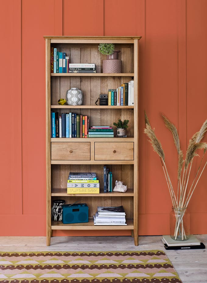 A solid pine bookcase that includes two drawers and decor besides book, against an terracotta hue accent wall. Image by Oakfurnitureland.