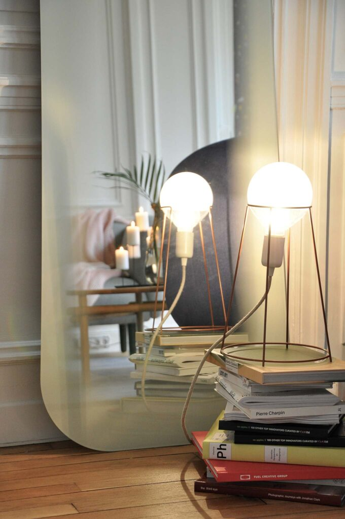 Detail of a floor mirror against a wall, with a stack of books in front and a table lamp with an exposed bulb atop