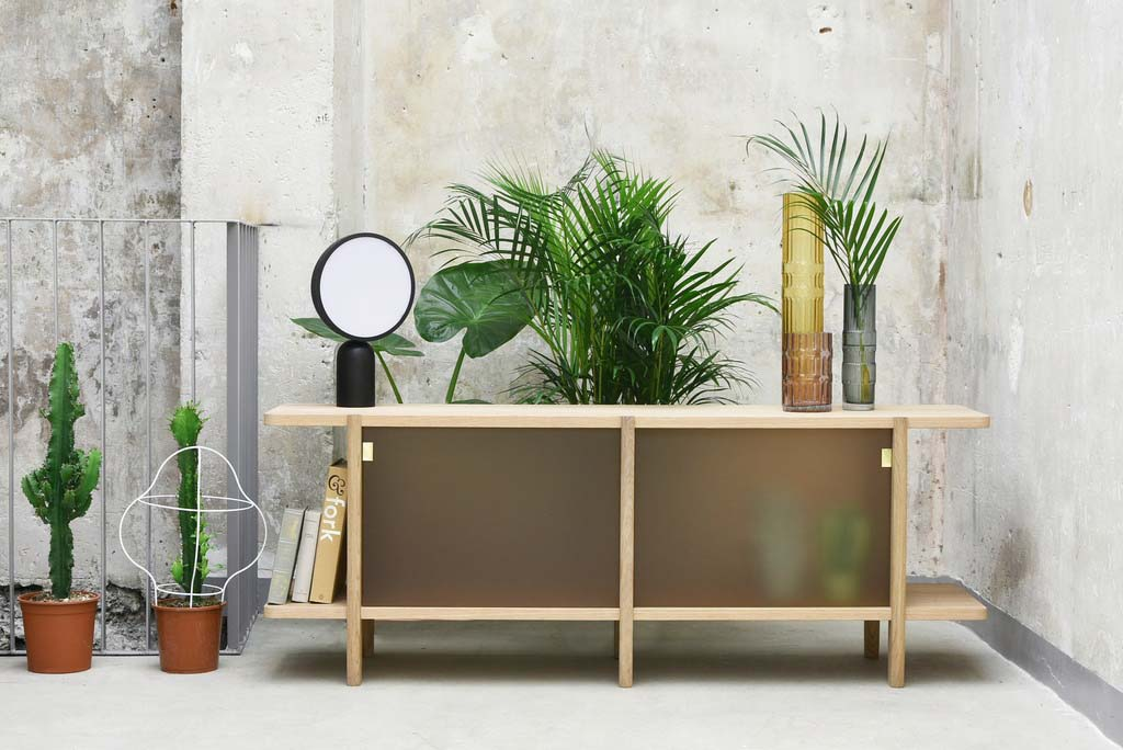 A wooden sideboard with glass doors and a cluster of three vases on the right and a table mirror on the left as decor all against a green plant behind the sideboard and a concrete accent wall