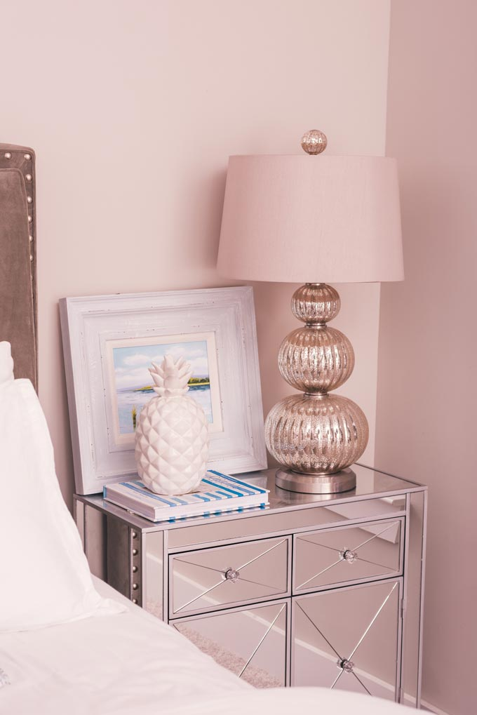 A powder pink vignette by a bed with a mirrored nightstand, stylish decor and table lamp.