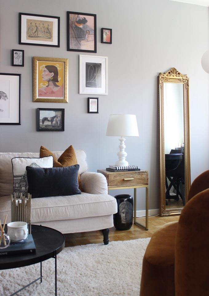 One of the six interior decorating fail proof tips calls for adding a mirror. A stylish living room with an art gallery wall and a mirror. Image by Cult Furniture.